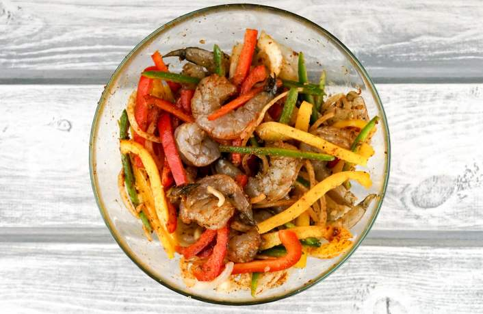 Shrimp mixed with homemade fajita seasoning for One Pan Shrimp Fajitas.
