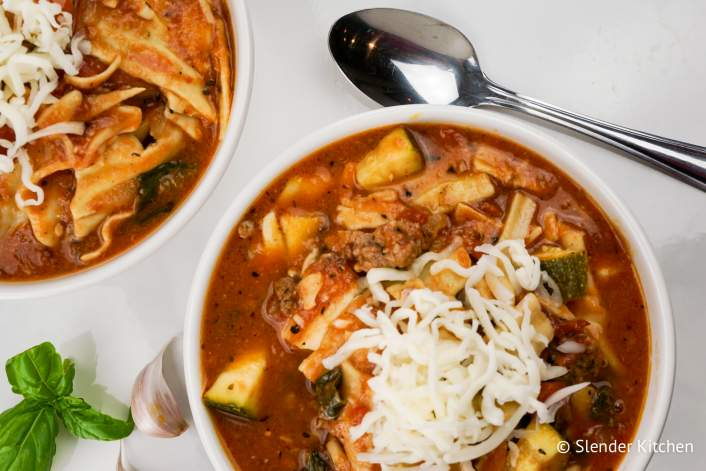 Healthy crockpot recipe for lasagna soup in two bowls with cheese.