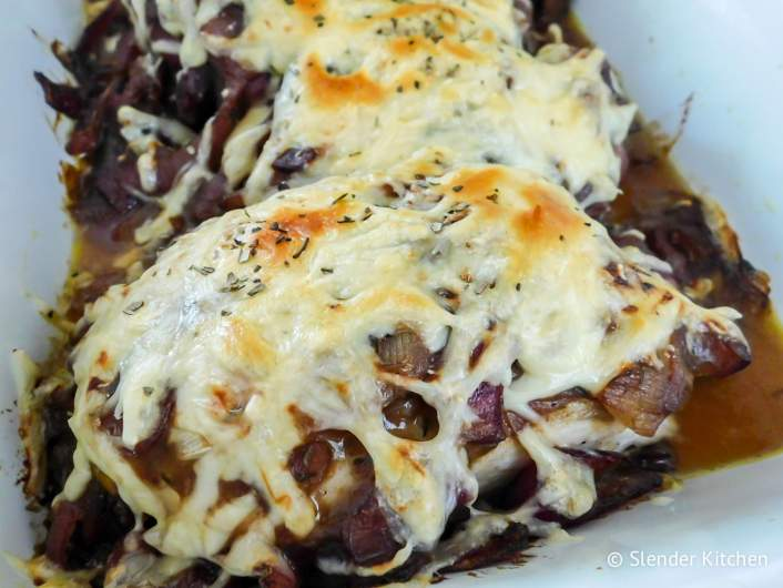 French Onion Soup Chicken on a plate with shredded melted cheese.